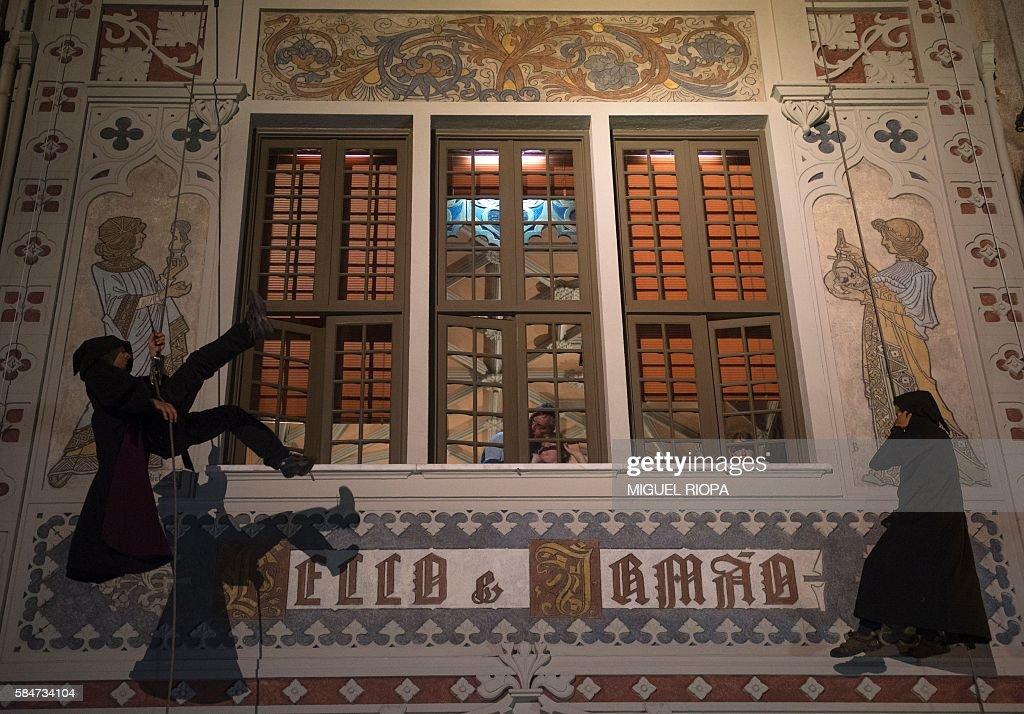 Actors costumed as characters of the famous series of Harry Potter fantasy novels by JK Rowling perform on July 31 2016 at the facade of Lello a...