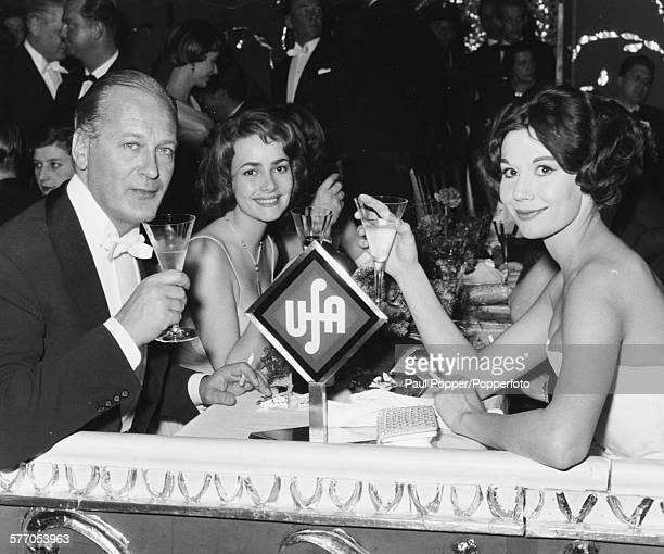 Actors Curd Jurgens Karin Dor and Simone Bucheron drink champagne together at the Munich Film Ball in the Deutschen Theatre Munich Germany on...