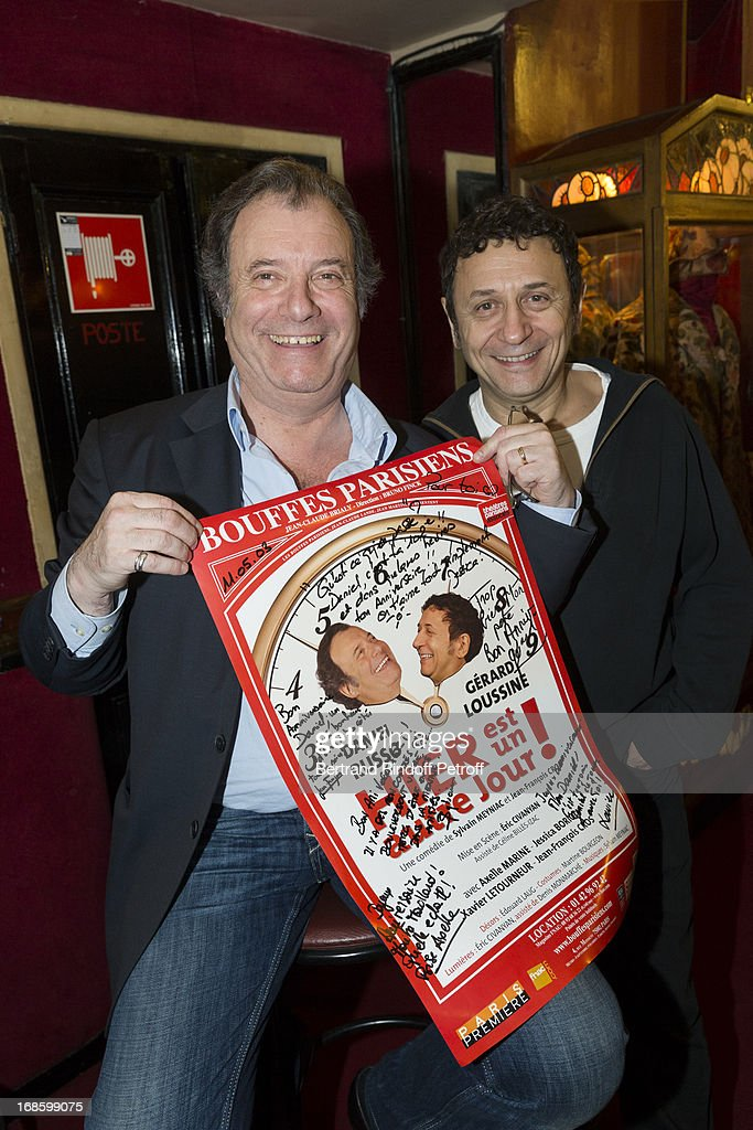 Actors Daniel Russo (L), holding the poster of the play, and Gerard Loussine pose following the 100th performance of the play 'Hier Est Un Autre Jour' at Theatre des Bouffes Parisiens on May 11, 2013 in Paris, France.