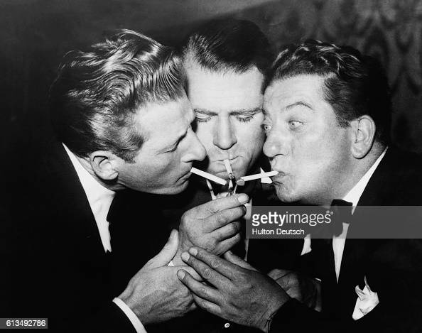 Actors Danny Kaye Laurence Olivier and Sid Field lighting a cigarette from a single match at the Cafe de Paris in London ca 1950's
