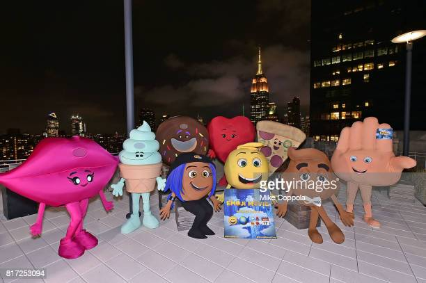 Actors dressed as Emoji characters pose for a photo at Sony Corporation NYC headquarters with Cast Of The Emoji Movie Girls Who Code And Oath For...