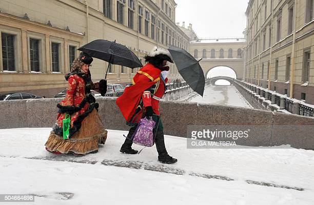 TOPSHOT Actors dressed as Tsar Peter the Great and Empress Catherine cross a snowcovered bridge in central St Petersburg on January 12 2016 / AFP /...