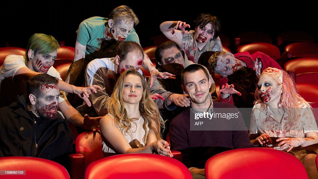 Actors dressed as zombies surround Australian actress Teresa Palmer (C-L) and British actor Nicholas Hoult (c-R) during a photo call for the film Warm Bodies in central London on January 18, 2013. AFP PHOTO/ANDREW COWIE