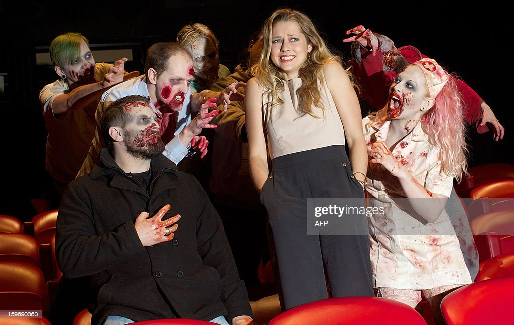 Actors dressed as zombies surround Australian actress Teresa Palmer (2nd R) during a photo call for the film Warm Bodies in central London on January 18, 2013.