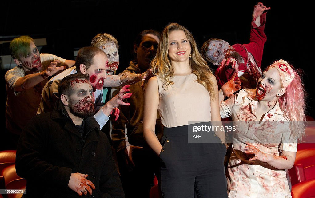Actors dressed as zombies surround Australian actress Teresa Palmer (2nd R) during a photo call for the film Warm Bodies in central London on January 18, 2013. AFP PHOTO/ANDREW COWIE