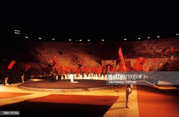 Actors dressed in white are waving red flags with high rods on the stage set in the middle of the Arena di Verona the show is a tribute to Maria...