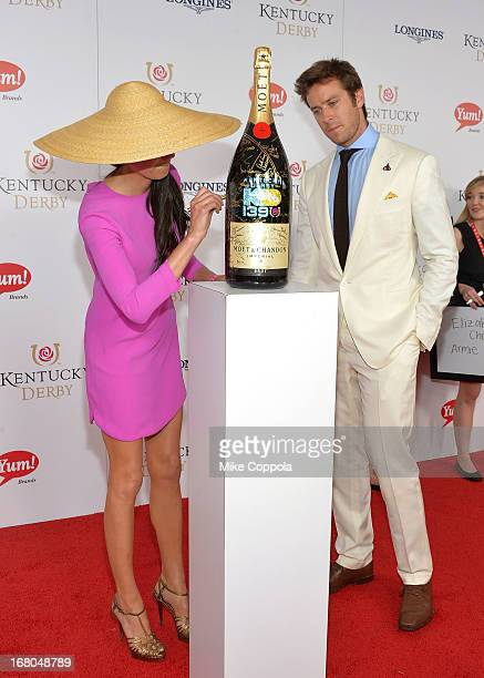 Actors Elizabeth Chambers and Armie Hammer sign the Moet Chandon 6L for the Churchill Downs Foundation during the 139th Kentucky Derby at Churchill...