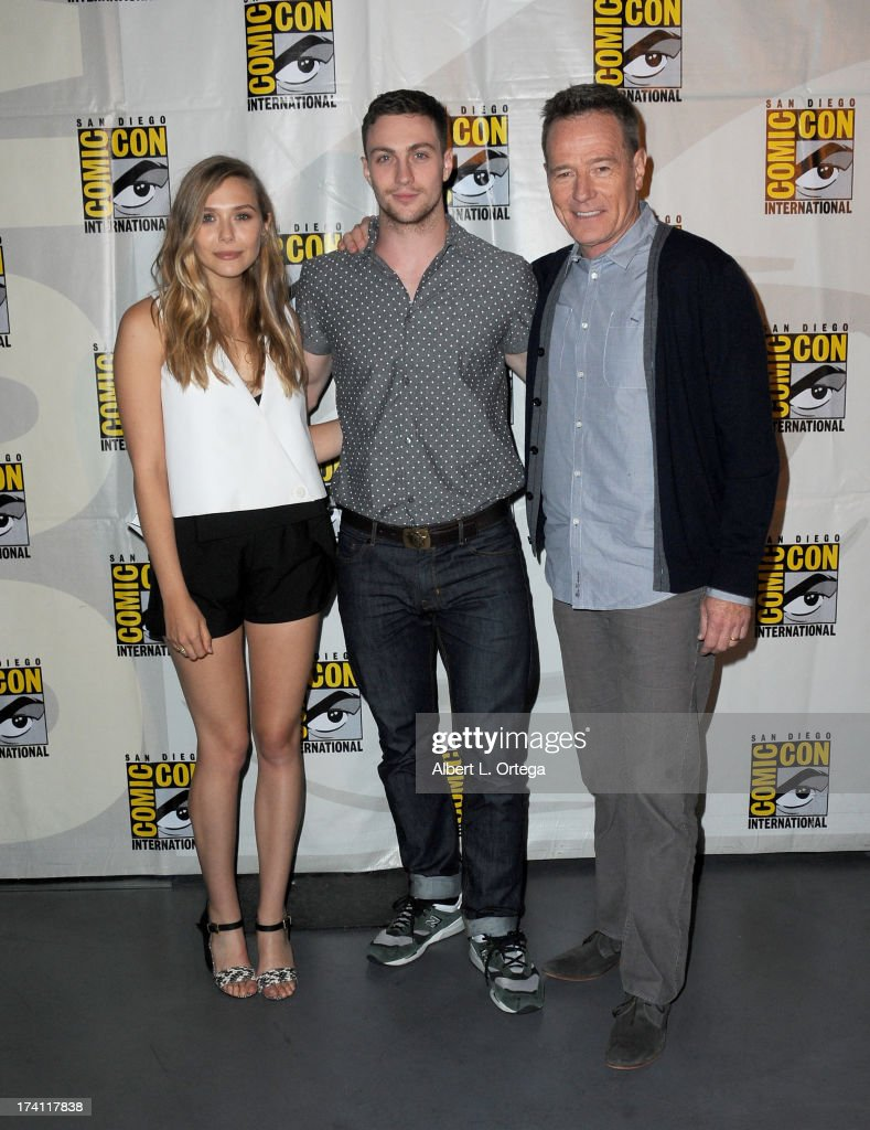 Actors Elizabeth Olsen, Aaron Taylor-Johnson, and Bryan Cranston pose backstage at the Warner Bros. and Legendary Pictures preview of 'Godzilla' during Comic-Con International 2013 at San Diego Convention Center on July 20, 2013 in San Diego, California.