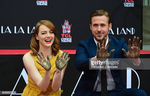 Actors Emma Stone and Ryan Gosling display their hands after placing them into the block of cement at their Hand and Foot prints ceremony in front of...