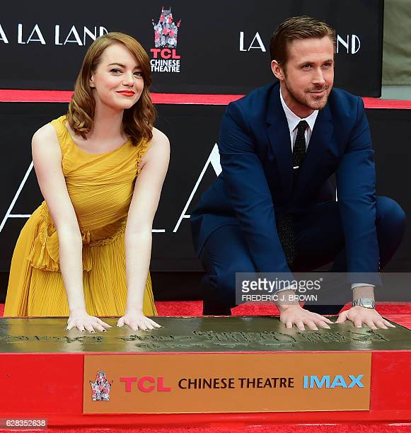 Actors Emma Stone and Ryan Gosling pose while placing their hands into the block of cement at their Hand and Foot prints ceremony in front of the TCL...