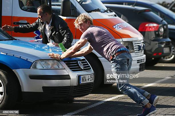 Actors Erdogan Atalay and Daniel Roesner push a car during the photocall for the action series 'Alarm Fuer Cobra 11' on August 31 2015 in Cologne...