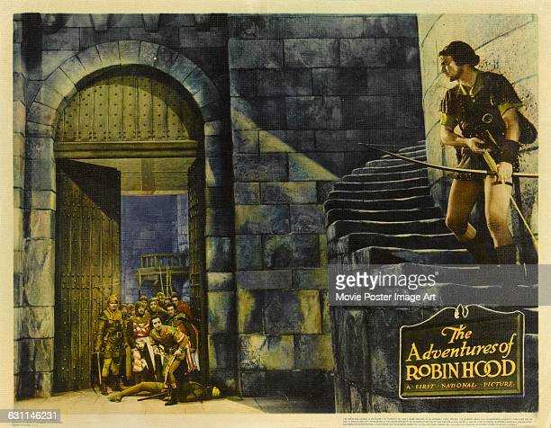 Actors Errol Flynn and Basil Rathbone appear on a poster for the 1938 adventure film 'The Adventures of Robin Hood' produced by Warner Bros