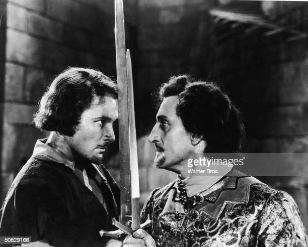 Actors Errol Flynn and Basil Rathbone face off for a duel in a still from the film 'The Adventures of Robin Hood' directed by Michael Curtiz and...