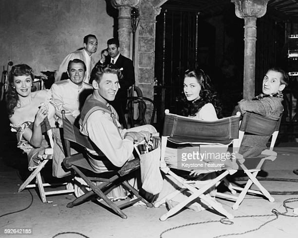 Actors Eve Arden Charles Kullman Jean Aumont Yvonne de Carlo and director Walter Reisch relaxing on the set of the film 'Song Of Scheherazade' in...