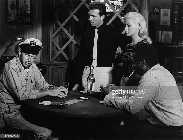 Actors Frank Sinatra Anthony Franciosa Virna Lisi and Errol John in a scene from the movie 'Assault On A Queen' in 1966