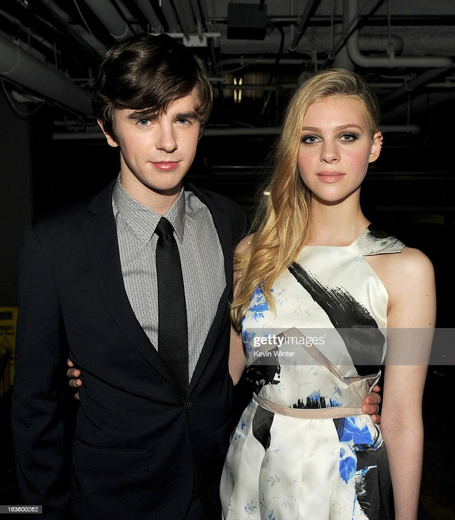 Actors Freddie Highmore (L) and Nicola Peltz arrive at the premiere of A&E Network's 'Bates Motel' at Soho House on March 12, 2013 in West Hollywood, California.