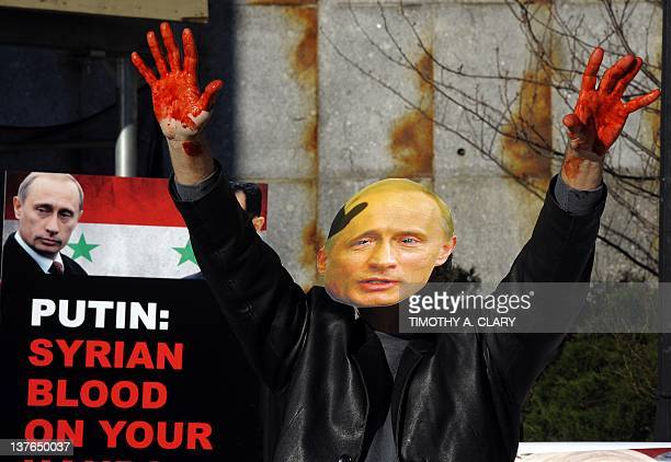 Actors from Avaaz wearing giant masks of Bashar alAssaz and Vladimir Putin dump dozens of bloodied body bags outside the UN Security Council building...