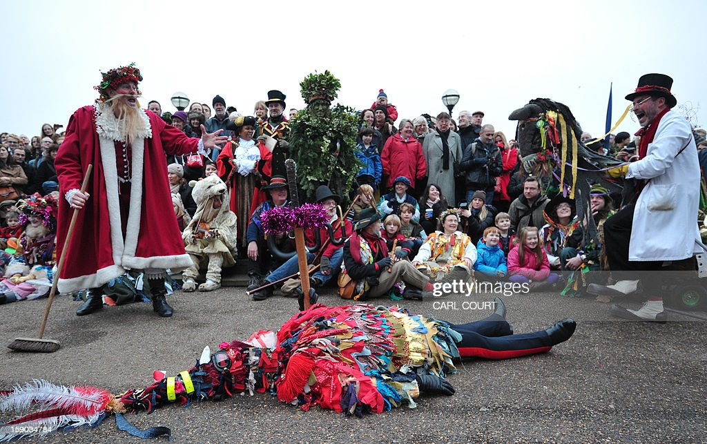 Actors from The Bankside Mummers group (from the Lions part) portraying St George, Santa Claus and a doctor perform in a folk play near the Globe Theatre in central London on January 6, 2013, in celebration of Twelfth Night, marking the end of the twelve days of winter festivities. Twelfth Night celebrations in the traditional agricultural calendar mark a last chance to make merry before returning to the rigours of work on Plough Monday.