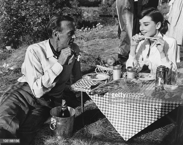 Actors Gary Cooper and Audrey Hepburn share a picnic on the set of the film 'Love in the Afternoon' being filmed on location in Paris 27th September...