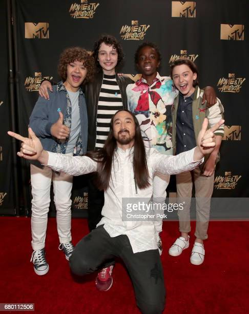 Actors Gaten Matarazzo Finn Wolfhard musician Steve Aoki and actors Caleb McLaughlin and Noah Schnapp attend the 2017 MTV Movie And TV Awards at The...