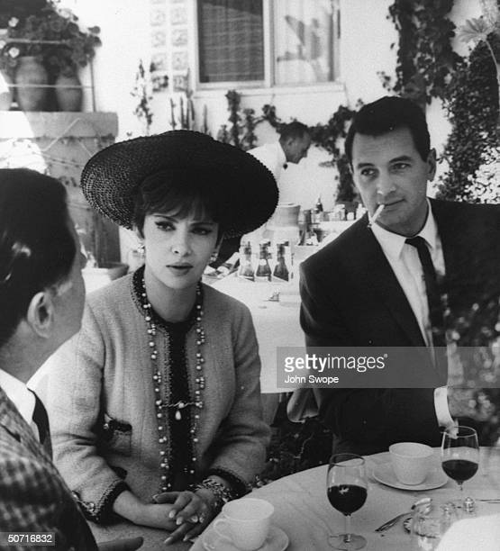 Actors Gina Lollobrigida and Rock Hudson sitting together at table during party