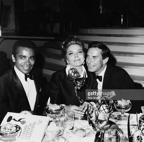Actors Greg Morris and Martin Landau sitting with actress Barbara Bain as she holds on to her award for the show 'Mission Impossible' at the Emmy...