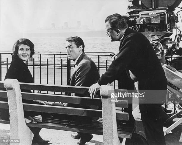 Actors Gregory Peck and Diane Baker sitting on a bench overlooking the sea as director Edward Dmytryk talks to them about the scene on the set of the...