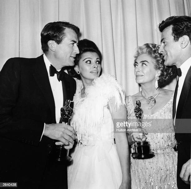Actors Gregory Peck Sophia Loren Joan Crawford and Maximilian Schell stand backstage at the Academy Awards Santa Monica Civic Auditorium Los Angeles...