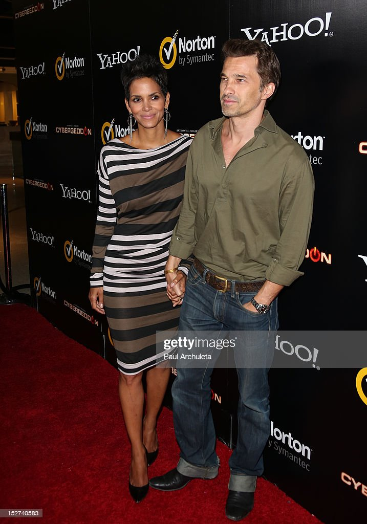 Actors <a gi-track='captionPersonalityLinkClicked' href=/galleries/search?phrase=Halle+Berry&family=editorial&specificpeople=201726 ng-click='$event.stopPropagation()'>Halle Berry</a> (L) and <a gi-track='captionPersonalityLinkClicked' href=/galleries/search?phrase=Olivier+Martinez&family=editorial&specificpeople=213013 ng-click='$event.stopPropagation()'>Olivier Martinez</a> (R) attend the 'Cybergeddon' premiere at the Pacific Design Center on September 24, 2012 in West Hollywood, California.