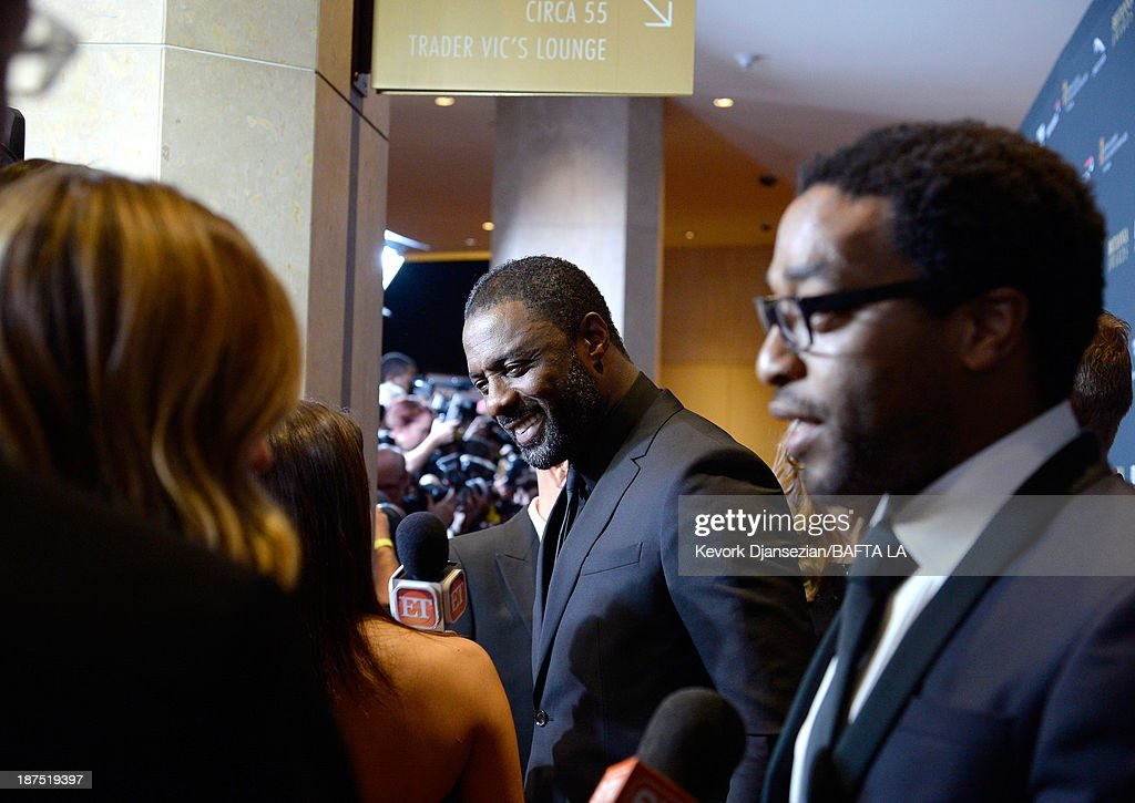 Actors Idris Elba (C) and Chiwetel Ejiofor attend the 2013 BAFTA LA Jaguar Britannia Awards presented by BBC America at The Beverly Hilton Hotel on November 9, 2013 in Beverly Hills, California.