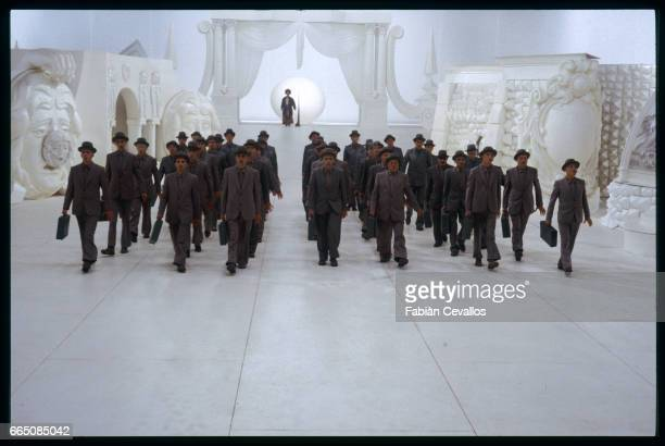 Actors in gray suits walk in rows as young German actress Radost Bokel stands in the background during the shooting of the movie Momo based on German...