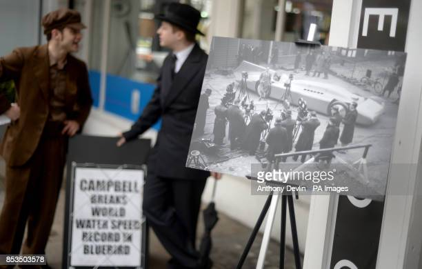 Actors in period costume pose beside a newspaper board reporting Sir Malcolm Campbell's world water speed record London