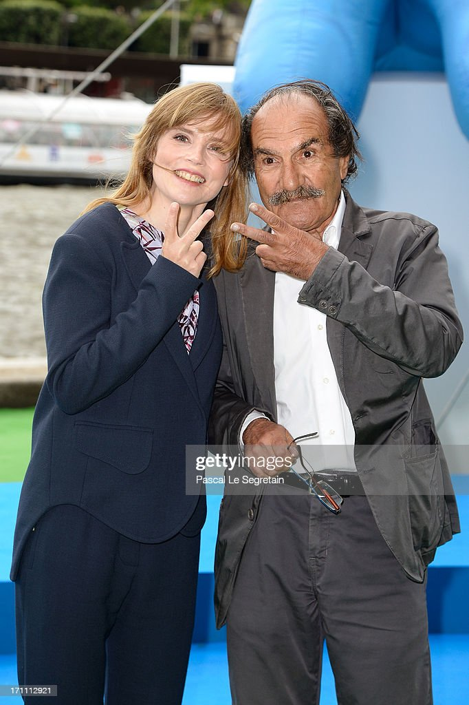 Actors Isabelle Carre (L) and Gerard Hernandez pose as part of Global Smurfs Day celebrations on the Seine river bank on June 22, 2013 in Paris, France. The Eiffel tower is seen behind.