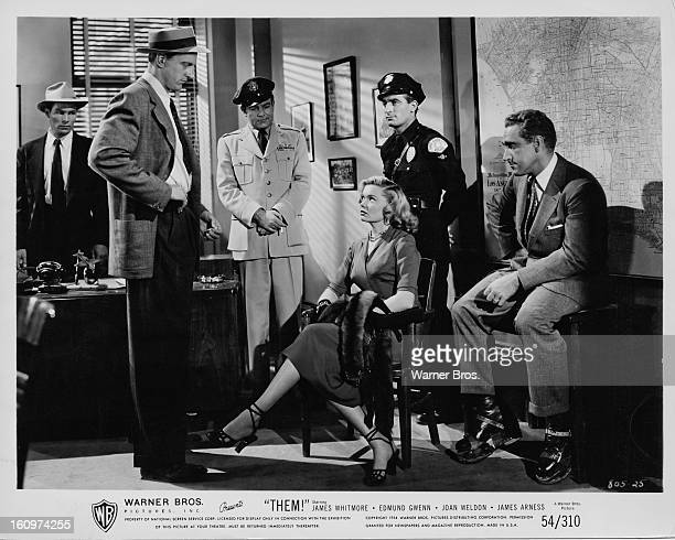 Actors James Arness and James Whitmore interview actress Mary Lou Holloway in a scene from the film 'Them' featuring giant mutant killer ants 1954...