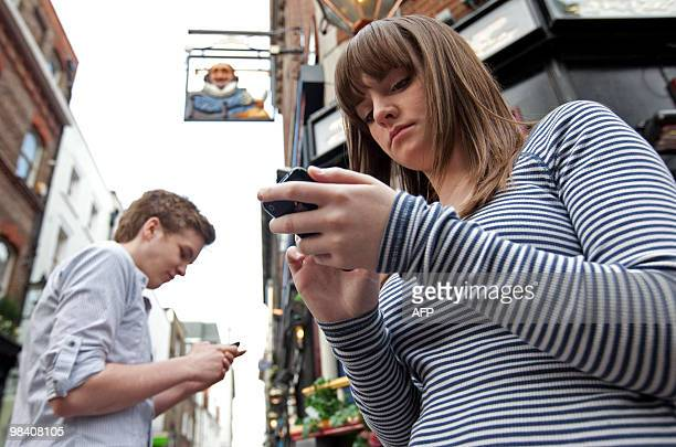 Actors James Barrett and Charlotte Wakefield use their phones as they play the roles of Rome and Juliet during a photocall for 'Such Tweet Sorrow' a...