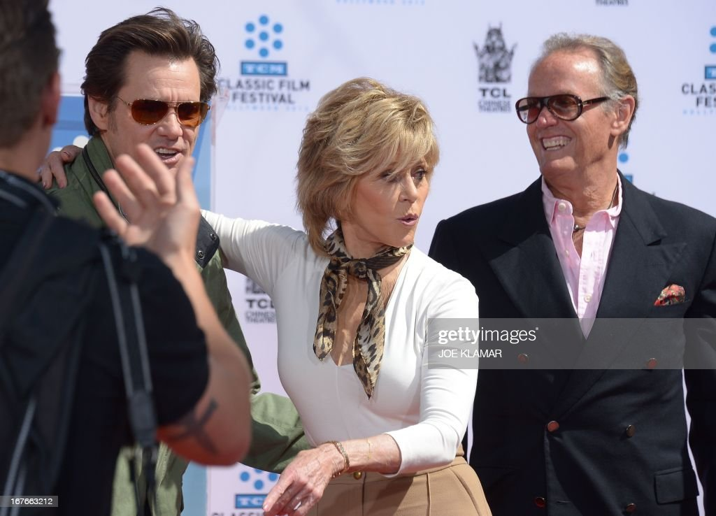 Actors Jim Carrey (L) and Peter Fonda (R) attend actress Jane Fonda's (C) Handprint/Footprint Ceremony during the 2013 TCM Classic Film Festival at TCL Chinese Theatre on April 27, 2013 in Los Angeles. Fonda is an American actress, writer, political activist, former fashion model, and fitness guru. She rose to fame in the 1960s with films such as Barbarella and Cat Ballou. She has won two Academy Awards, an Emmy Award, three Golden Globes and received several other movie awards and nominations during more than 50 years as an actress. After 15 years of retirement, she returned to film in 2005 with Monster-in-Law, followed by Georgia Rule two years later. She also produced and starred in over 20 exercise videos released between 1982 and 1995, and once again in 2010.