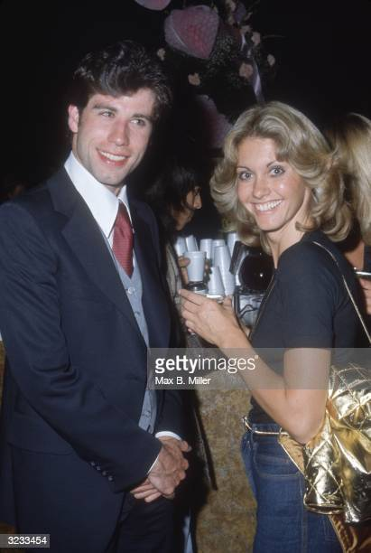Actors John Travolta and Olivia NewtonJohn stand at a bar at a party for the film 'Grease' in which they both starred Travolta is wearing a suit and...