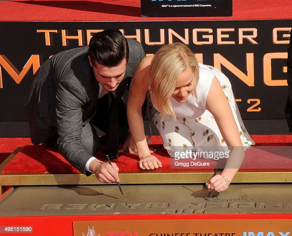 Actors Josh Hutcherson and Jennifer Lawrence pose at 'The Hunger Games Mockingjay Part 2' Hand And Footprint Ceremony at TCL Chinese Theatre on...