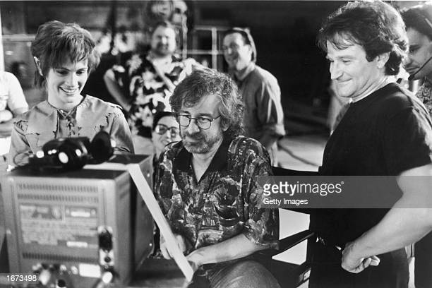 Actors Julia Roberts and Robin Williams watch daily production footage with director Steven Spielberg on the set of his film 'Hook' 1991