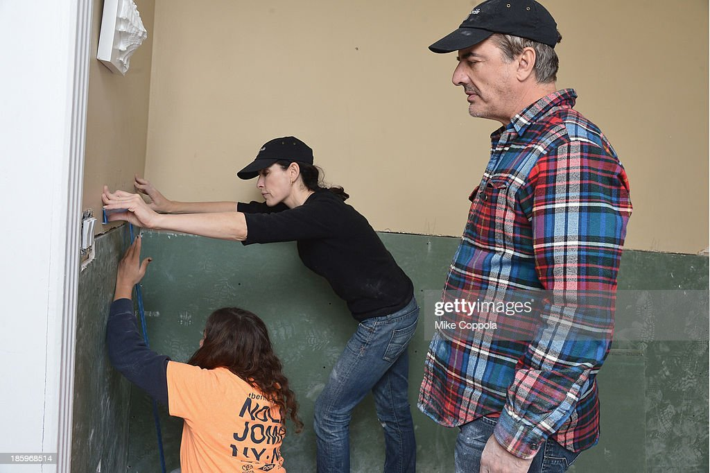 Actors <a gi-track='captionPersonalityLinkClicked' href=/galleries/search?phrase=Julianna+Margulies&family=editorial&specificpeople=208994 ng-click='$event.stopPropagation()'>Julianna Margulies</a> and <a gi-track='captionPersonalityLinkClicked' href=/galleries/search?phrase=Chris+Noth&family=editorial&specificpeople=206568 ng-click='$event.stopPropagation()'>Chris Noth</a> help repair a home as The Cast Of 'The Good Wife' Celebrates Their100th Episode With A Day Of Service For The St. Bernard Projecton on October 26, 2013 in New York City.