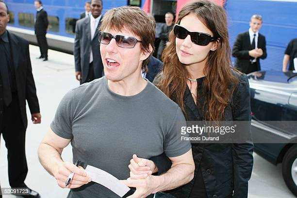 Actors Katie Holmes and fiance Tom Cruise sign autographs as they prepare to board a train at a Paris railway station ahead of the French premiere of...