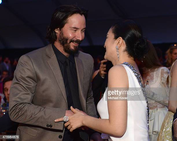 Actors Keanu Reeves and Li Gong wearing Piaget attend the 2014 Film Independent Spirit Awards at Santa Monica Beach on March 1 2014 in Santa Monica...