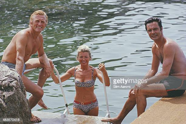Actors Kirk Douglas Louis Jourdan and Jourdan's wife Quiquie enjoying the water at the Hotel du CapEdenRoc in Antibes on the French Riviera August...