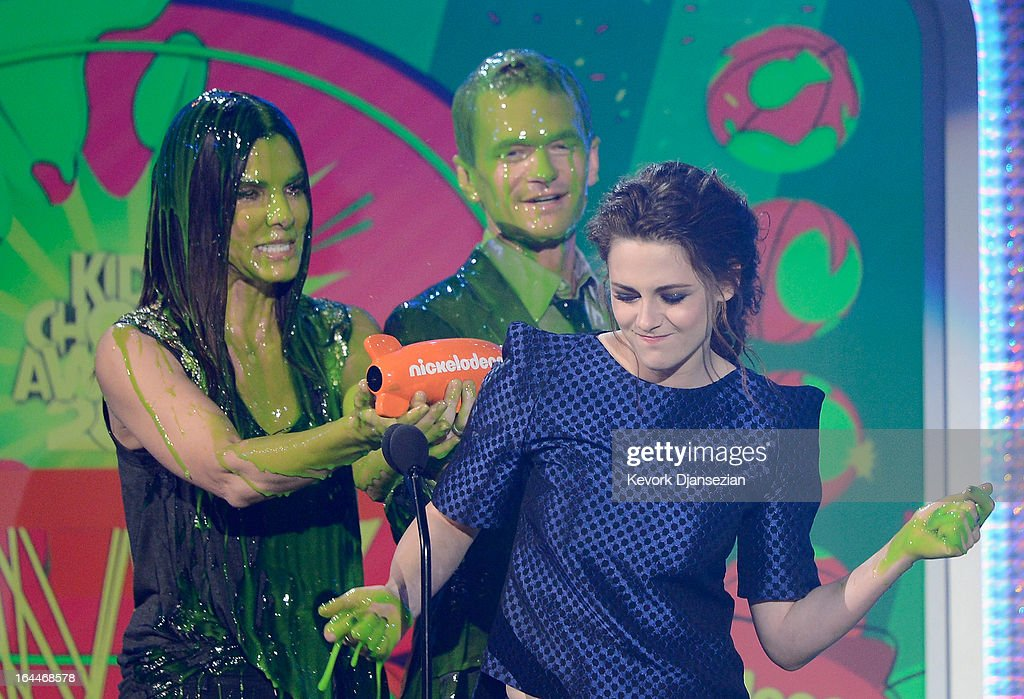 Actors Kristen Stewart (R), winner of Favorite Movie Actress for 'The Twilight Saga: Breaking Dawn – Part 2,' with Sandra Bullock and Neil Patrick Harris get slimed onstage during Nickelodeon's 26th Annual Kids' Choice Awards at USC Galen Center on March 23, 2013 in Los Angeles, California.