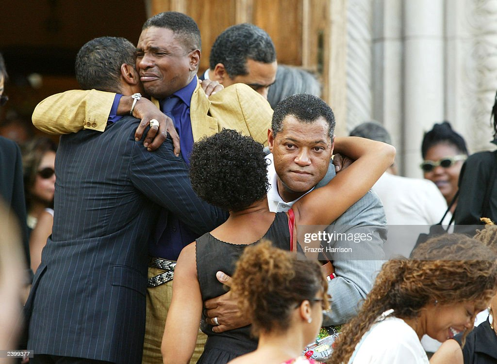 Actors Laurence Fishburne (4th from L) and actor Keith David (2nd from L) hug mourners at the memorial service at Saint Monica's Catholic Church held for actor/dancer Gregory Hines on August 13, 2003 in Santa Monica, California.