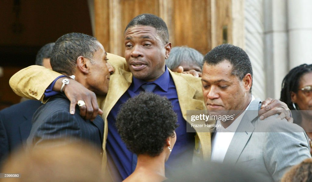 Actors Laurence Fishburne (R) is hugged by actor Keith David (C) at the memorial service at Saint Monica's Catholic Church held for actor/dancer Gregory Hines on August 13, 2003 in Santa Monica, California.