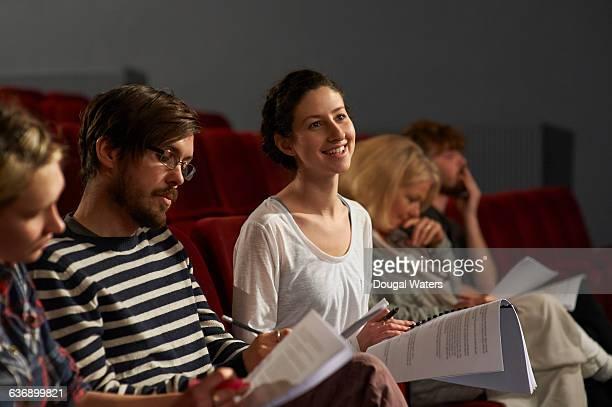 Actors learning script in theatre.