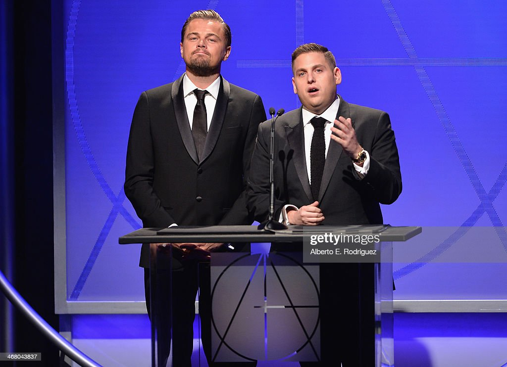 Actors <a gi-track='captionPersonalityLinkClicked' href=/galleries/search?phrase=Leonardo+DiCaprio&family=editorial&specificpeople=201635 ng-click='$event.stopPropagation()'>Leonardo DiCaprio</a> and <a gi-track='captionPersonalityLinkClicked' href=/galleries/search?phrase=Jonah+Hill&family=editorial&specificpeople=544481 ng-click='$event.stopPropagation()'>Jonah Hill</a> speak on stage atthe 18th Annual Art Directors Guild Exellence In Production Design Awards at The Beverly Hilton Hotel on February 8, 2014 in Beverly Hills, California.