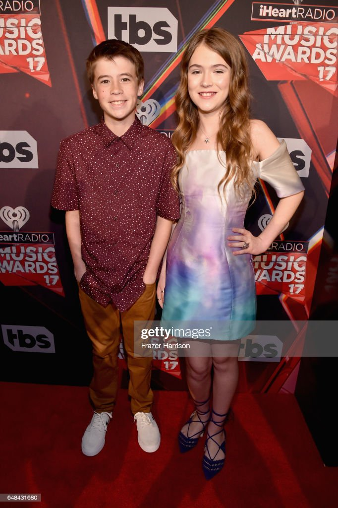 Actors Liam Carroll (L) and Ashley Gerasimovich attend the 2017 iHeartRadio Music Awards which broadcast live on Turner's TBS, TNT, and truTV at The Forum on March 5, 2017 in Inglewood, California.