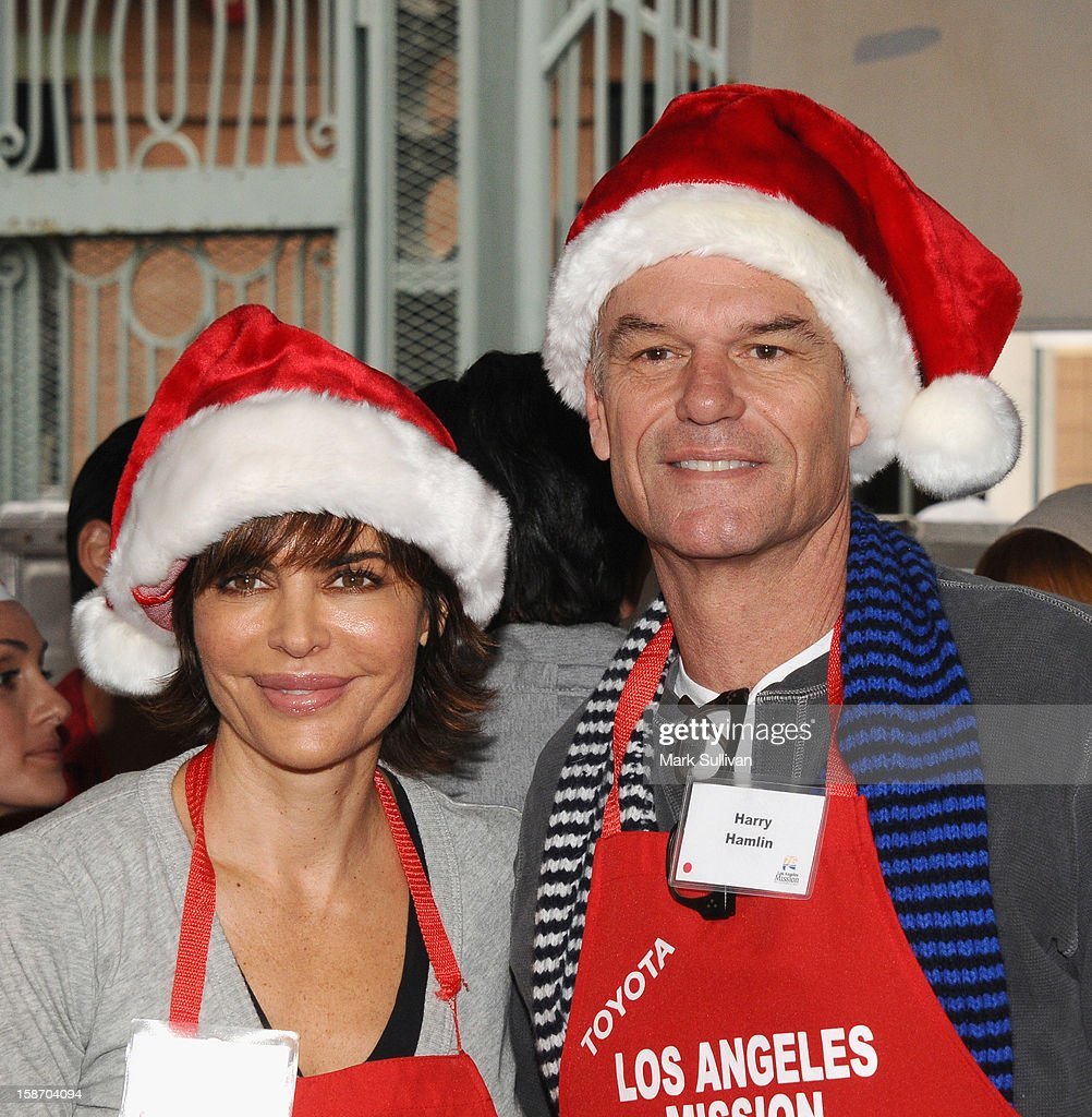 Actors Lisa Rinna and Harry Hamlin serve food during the Los Angeles Mission Christmas Eve meal for the homeless at Los Angeles Mission on December 24, 2012 in Los Angeles, California.